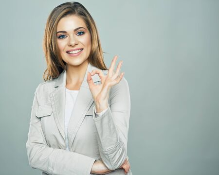 Business woman show ok symbol. Toothy smiling business woman portrait. Stockfoto