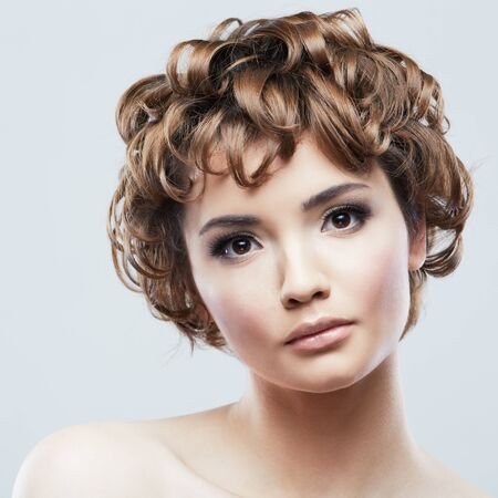 Retrato de belleza de mujer. Ciérrese encima de la cara de la mujer aislada en blanco. Hermosa chica de pelo corto. Foto de archivo