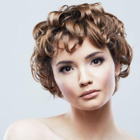 Schönheitsporträt der Frau. Schließen Sie herauf das Gesicht der Frau, das auf Weiß lokalisiert wird. Schönes Mädchen mit kurzen Haaren. Standard-Bild