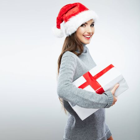 Christmas isolated woman portrait hold red christmas gift. Smiling happy girl on white background. Stock Photo
