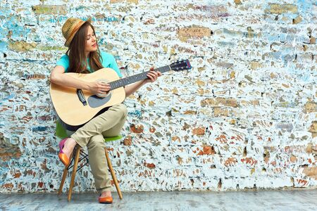 Young woman sitting on chair play guitar. Vintage brick wall background. Stock Photo