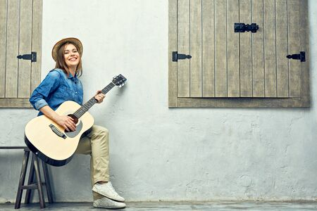 Happy young woman with guitar street portrait. Stock Photo