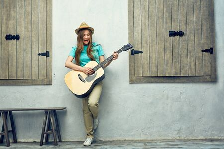Young woman guitar play. Hipster girl portrait on street.