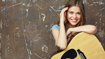 Close up face portrait of smiling girl with guitar. Grunge background.