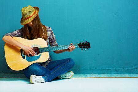 Girl fashion portrait. Model play guitar. Blue background.