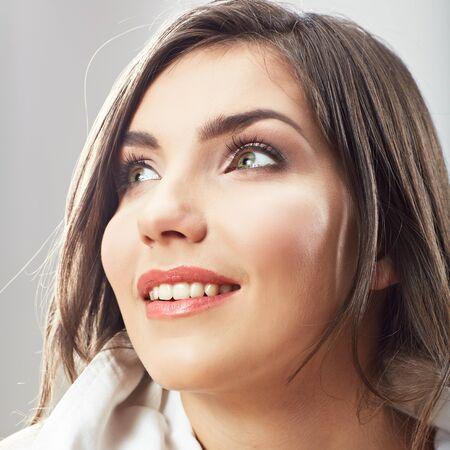 Woman face close up white backround isolated. Smiling girl portrait. Female model studio poses.