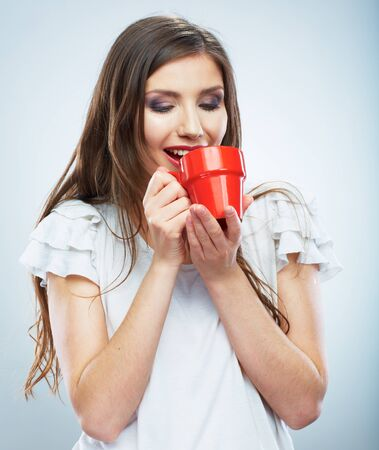 Coffee cup. Young woman on isolated studio background. Beautiful girl portrait. Female model poses. Banco de Imagens