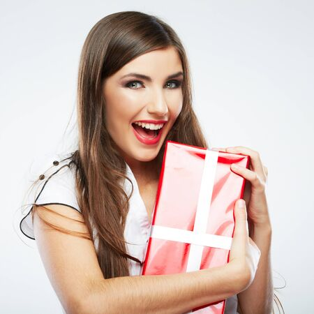 Young woman portrait hold christmas gift. Smiling happy girl on white background. Long hair female model.