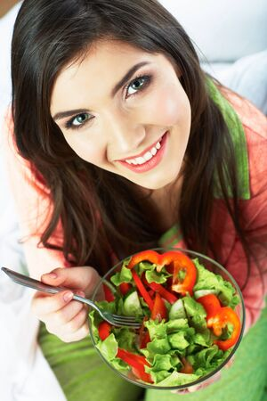 Young woman eat vegetarian food. Green salad..