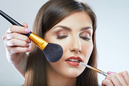 Beautiful woman faceclose up portrait. Make up applying with brush. Isolated.
