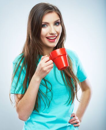 Coffee cup. Young woman on isolated studio background. Beautiful girl portrait. Female model poses. Stock Photo