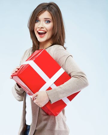 Portrait of young happy smiling woman hold red gift box. Isolated studio background female model.