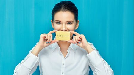 businesswoman wearing white shirt holding credit card. blue wall background.