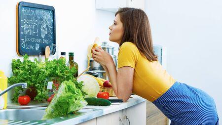Woman in kitchen eating banana. Breakfast cooking. Stockfoto