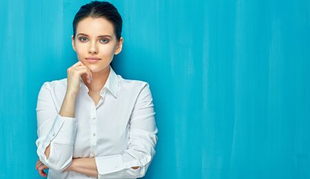 Woman wearing white shirt standing on blue wall background.