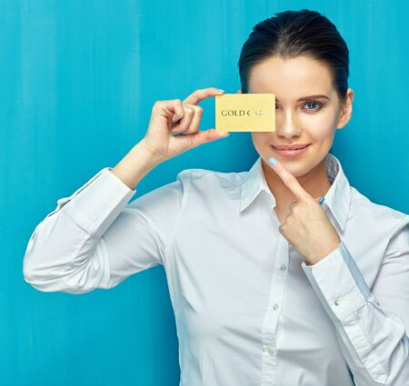 businesswoman wearing white shirt holding credit card near eye and pointing finger. blue wall background.