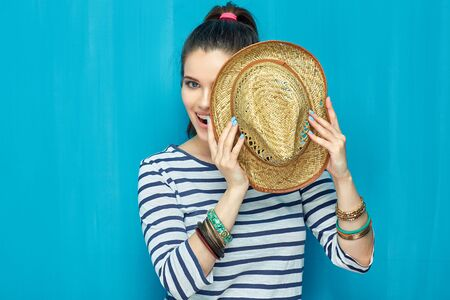 Smiling Teenager girl portrait with hat on blue wall background.