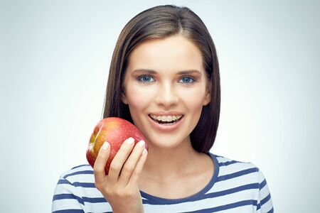 Smiling girl with dental braces holding red apple. Isolated portrait.