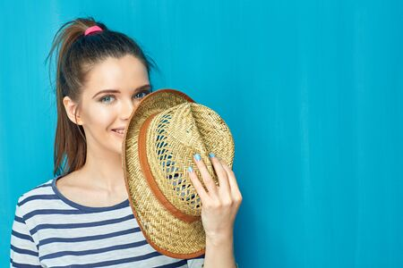 Close up face portrait of smiling teen girl holding hat. Blue wall background.