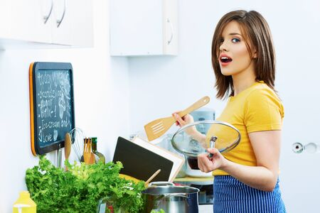 Portrait of young cooking woman in kitchen. Beautiful smiling housewife.
