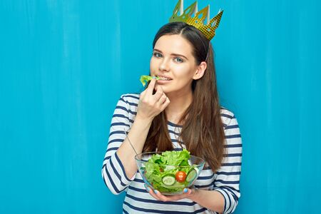 Smiling girl wearing paper crown eating salad. Blue wall background.