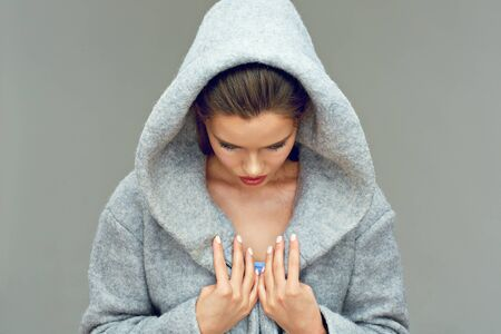 Young woman wearing hood looking down. Isolated portrait.