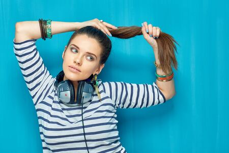Beautiful girl with headphones, tail hair style. Portrait teenager style on blue.