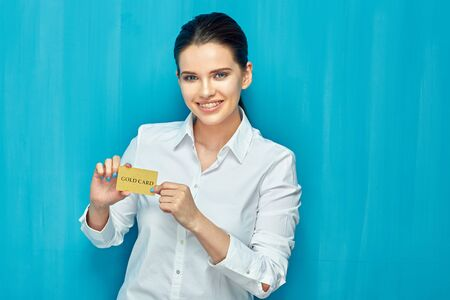 Young woman wearing white shirt holding credit card. Blue wall background. Stockfoto