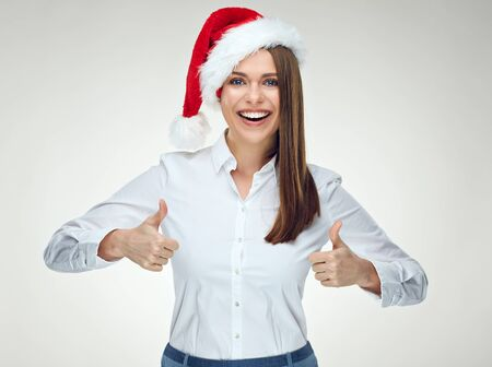 Smiling businesswoman wearing santa hat showing thumb up. Isolated portrait on white.
