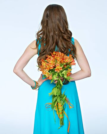 Woman with flowers standing back on white background. Long hair. Blue dress.