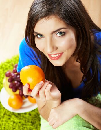 Woman seating on floor with fruits. Female model indoor portrait. Фото со стока