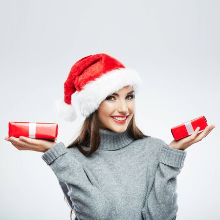 Christmas isolated woman portrait hold red christmas gift. Smiling happy girl on white background. Foto de archivo