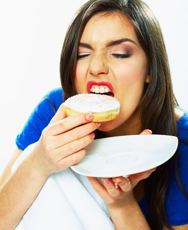 Woman bite donut. Close up portrait of young woman holding plate with donut. Foto de archivo