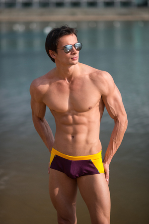 naked male body: Portrait of an athletic, muscular sexy man in swimtrunks Stock Photo