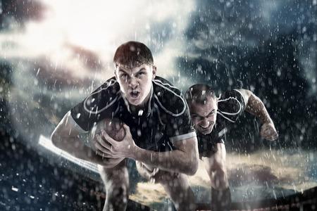Gli atleti, i giocatori di rugby in esecuzione sotto la pioggia intorno allo stadio con la palla, wrestling