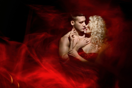 sex activity: Young beautiful couple in love posing against a dark background in a red dress and bright red rays like fire
