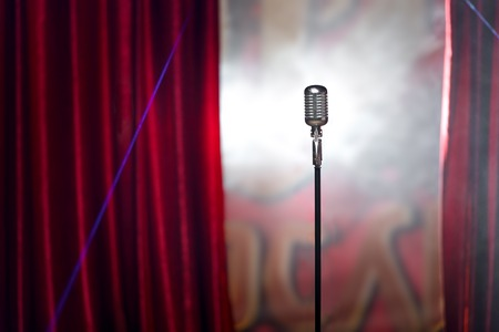 the microphone in front of red curtain on an empty stage after the concert, smoke 版權商用圖片