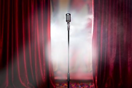 cortinas rojas: el micrófono delante de la cortina roja en un escenario vacío después del concierto, el humo Foto de archivo