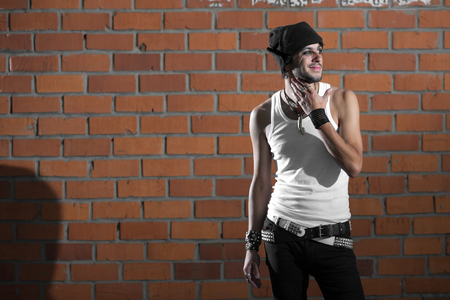 spiky hair: punk rocker stylish man in the white T-shirt and black jeans with red urban brick wall background