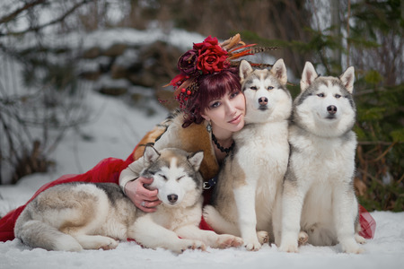 husky: Beautiful woman in red dress with a husky dogs, looks like a wolfs Stock Photo
