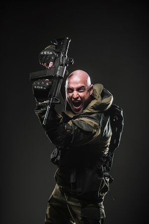 bombing: Military, war, conflict, soldiers - Special forces soldier man hold Machine gun on a  dark background. Military equipment of Russian soldiers Stock Photo