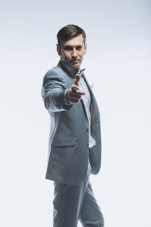 suitor: Portrait of a elegant handsome businessman in a gray suit on white background
