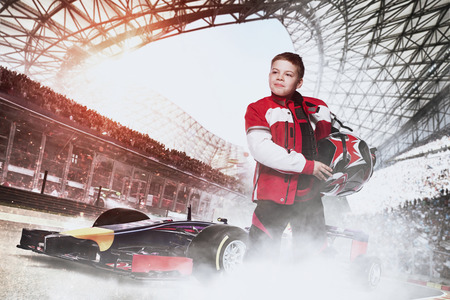 Race car or bike driver. The boy in the costume of the racer holding a helmet and looking at the camera