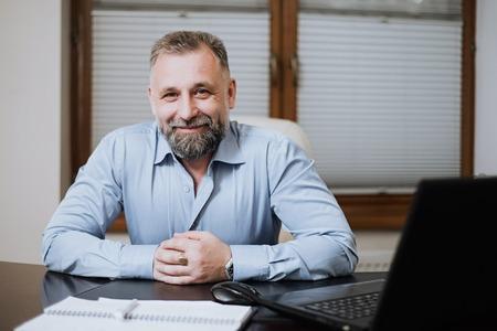 Ritratto di solido uomo d'affari di mezza età. Direttore dell'organizzazione nel suo ufficio