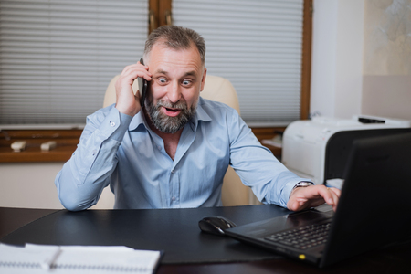 emotionally: Businessman in his office is emotionally talking on the phone