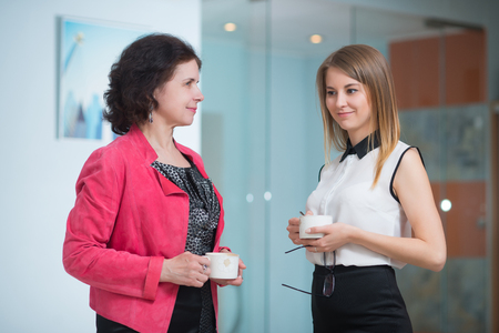break in: Work colleagues chatting while enjoying coffee break in the office Stock Photo
