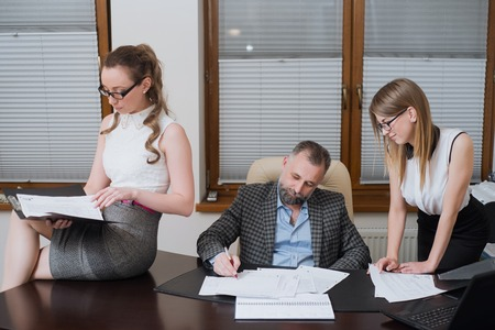 Businessman and his assistants secretaries in his office. The secretaries brought the boss documents to sign Stock Photo