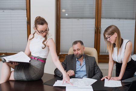 Businessman and his assistants secretaries in his office. The secretaries brought the boss documents to sign Фото со стока