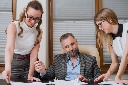 registrar: Businessman and his assistants secretaries in his office. The secretaries brought the boss documents to sign Stock Photo