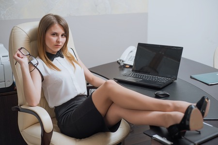 skirts: a very beautiful and sexy business woman sitting with her feet on the desk Stock Photo